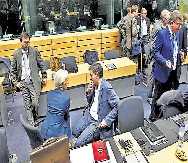 ब्रुसेल्स  युरोझोनच्या अर्थमंत्र्यांच्या बैठकीत आंतरराष्ट्रीय नाणेनिधीचे संचालक ख्रिस्टिन लगार्ड (मध्यभागी) यांच्याशी चर्चा करताना ग्रीसचे अर्थमंत्री साकालोटॉस. - Divya Marathi