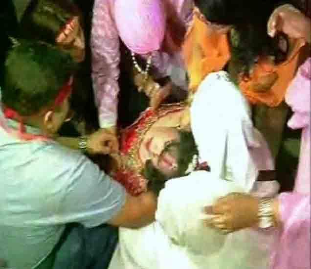 राधे मॉं खाली कोसळताना तिला उचलताना भाविक. - Divya Marathi