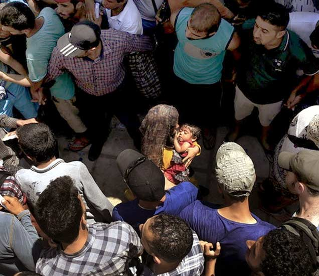 ग्रीकच्या कोस आयलंडमध्ये रजिस्ट्रेशन प्रोसेसदरम्यान गर्दीमध्ये बाळासह अडकलेल्या एका महिलेला चारही बाजुने घेराव घालून तिचा असा बचाव केला. - Divya Marathi