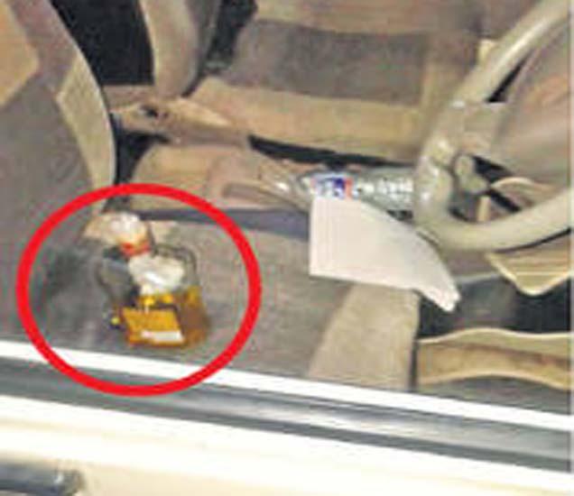 पोलिस गाडीत आढळलेली मद्याची बाटली. - Divya Marathi