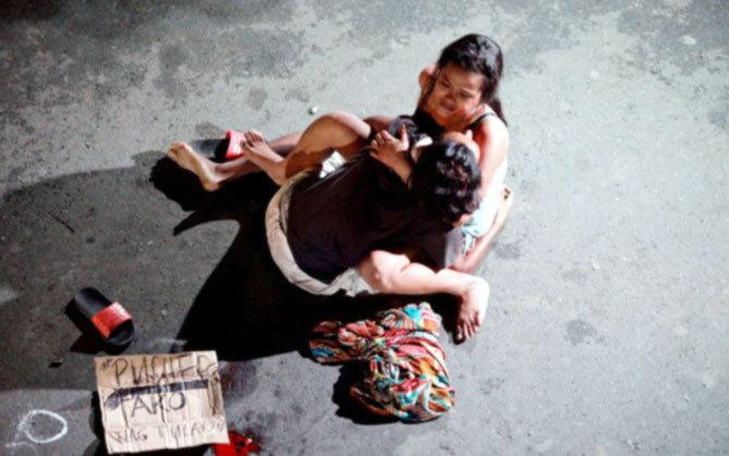 पतीच्या हत्येमुळे रस्त्यावर रडत असलेल्या या महिलेचा छायाचित्र दुतेर्तेची निर्दयतेचा मुखवटा आहे. (फाईल) - Divya Marathi