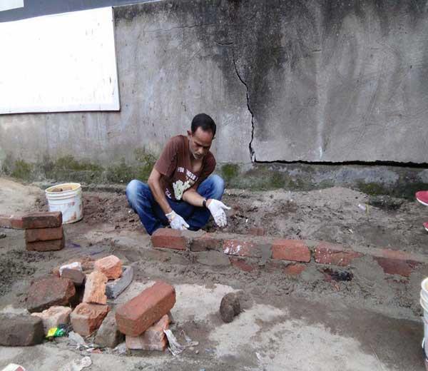 या फोटोत नरेंद्र धोनी वाळू, सिमेंटचा वापर करुन भिंत बांधत असल्याचे दिसत आहे. - Divya Marathi