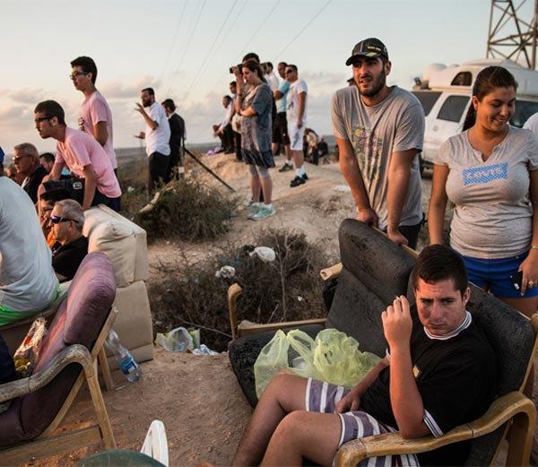 पॅलेस्टाईनवर होत असलेले बॉम्बहल्ले सोफा-खुर्चीवर बसून पाहताना लोक.... - Divya Marathi