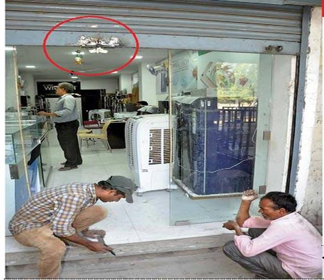 चोरट्यांनी टॉमीच्या साह्याने उचकवलेल्या शटरचा भाग (वर्तुळात). तसेच शटरचे लाॅक अधिक मजबूत करून दुरुस्ती करताना कारागीर. - Divya Marathi