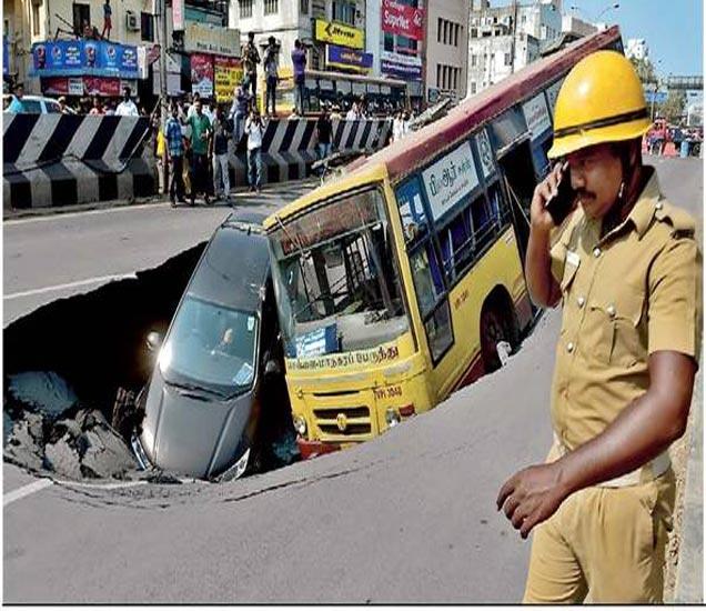 अण्णा सलाई रस्त्यावर अचानक रस्ता खचल्याने एक बस आणि कार खड्ड्यात पडली. - Divya Marathi