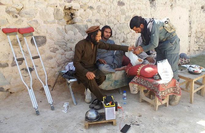 अमेरिकेच्या हल्ल्यात एक अफगाणिस्तानी पोलीस सुद्धा जखमी झाला. त्यावर उपचार करताना वैद्यकीय कर्मचारी - Divya Marathi
