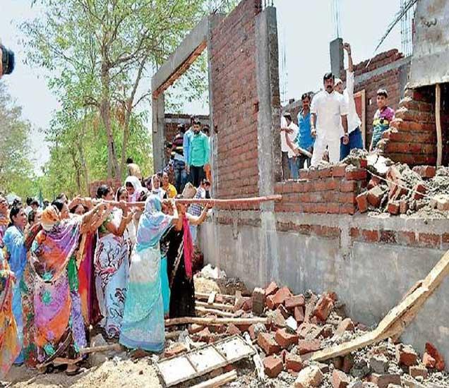 कोळवले नगरातील बांधकाम बांबूच्या साहाय्याने पाडताना संतप्त महिला. - Divya Marathi