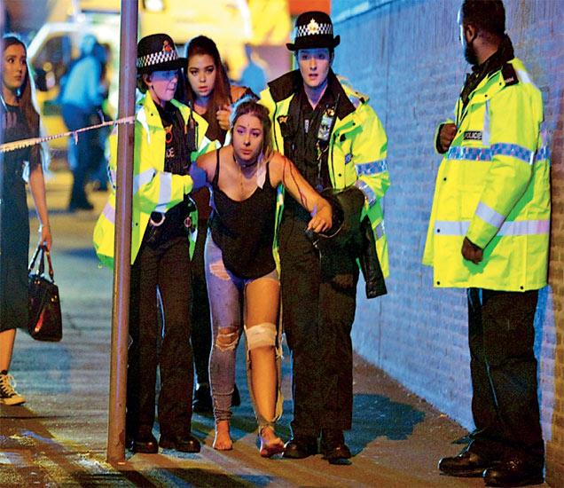 मँचेस्टरमध्ये पॉप स्टार अॅरियाना ग्रँडच्या काॅन्सर्टमधील आत्मघाती स्फोटात जखमी झालेल्या तरुणीला मदत करताना ब्रिटिश पोलिस. - Divya Marathi