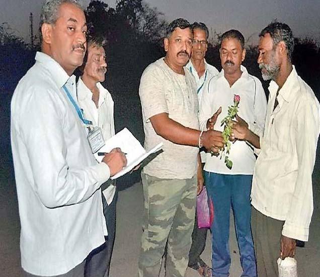 उघड्यावर शौचास जाणाऱ्यास गुलाबपुष्प देताना पथक - Divya Marathi