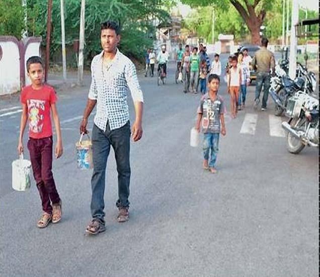 हातात लहान बकेट घेऊन नागरिक मुले असे रस्त्यावर अाले. - Divya Marathi