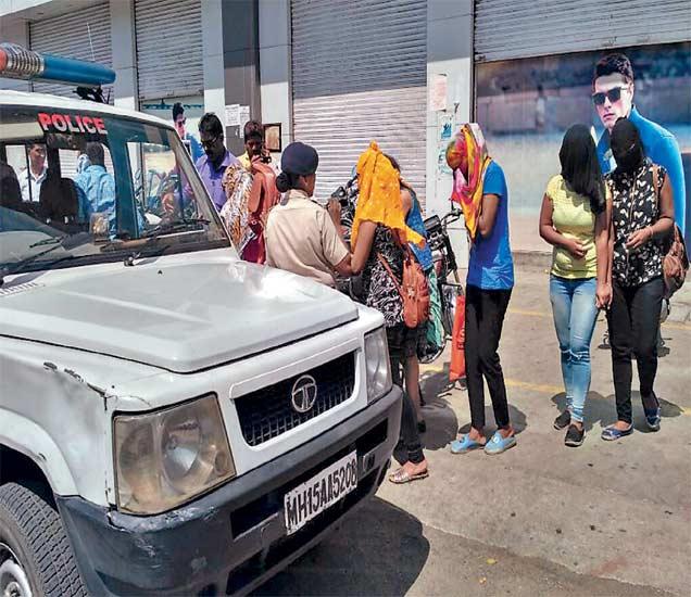 नाशिकमधील स्पा सेंटरमध्ये पकडल्यानंतर ताेंड लपवताना तरुणी. - Divya Marathi
