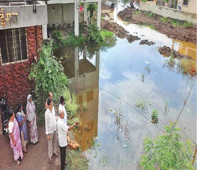 नगर-कल्याण रस्त्यावरील अनेक वसाहतींमध्ये मोठ्या प्रमाणात पावसाचे पाणी साचले आहे. (छायाचित्रे : मंदार साबळे) - Divya Marathi