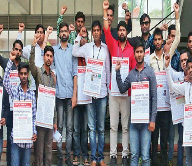 मुक्त विद्यापीठातील घाेटाळ्यांची चाैकशी करावी या मागणीसाठी 'दिव्य मराठी'तील बातम्यांचे पाेस्टर्स गळ्यात अडकवून अांदाेलन करताना मनविसेचे पदाधिकारी. - Divya Marathi