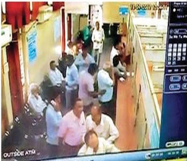 स्टेट बँकेच्या कॅश काउंटरवर उभ्या असलेल्या कर्मचाऱ्यास बोट लावून खुणावताना चोरटा. - Divya Marathi