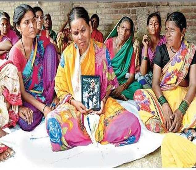 जवान सुमेध गवईंची प्रतिमा जवळ घेतलेल्या त्यांच्या शोकाकूल आईसह आप्त,महिला. - Divya Marathi