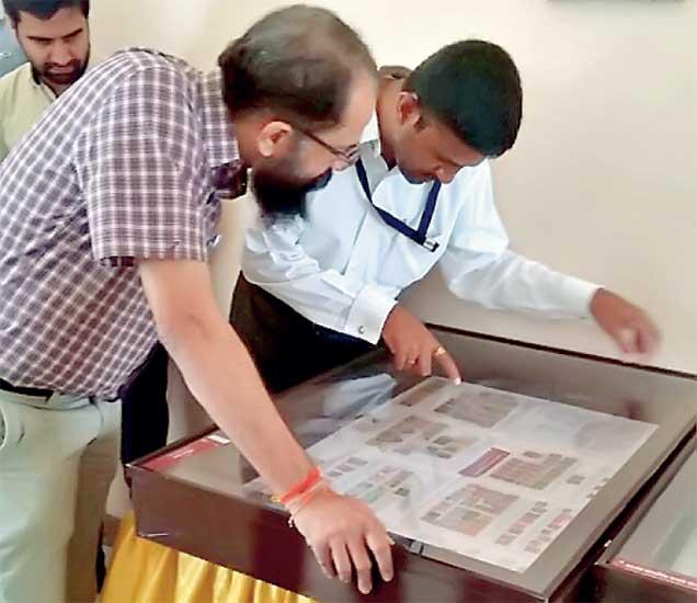 वस्तुसंग्राहक सचिन डागा यांचे नाणी, नोटा तिकिटांचे प्रदर्शन पाहताना जिल्हाधिकारी अभय महाजन. - Divya Marathi