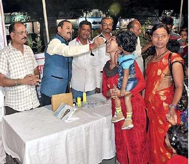 महिला भाविकास स्वाइन फ्लूचा डोस देताना जिल्हाधिकारी. - Divya Marathi