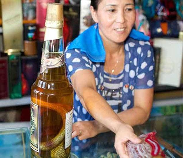 या देशात अल्कोहोल बॅन आहे, मात्र या दुकानात ही महिला स्नेक वोडका विक्री करत आहे. - Divya Marathi