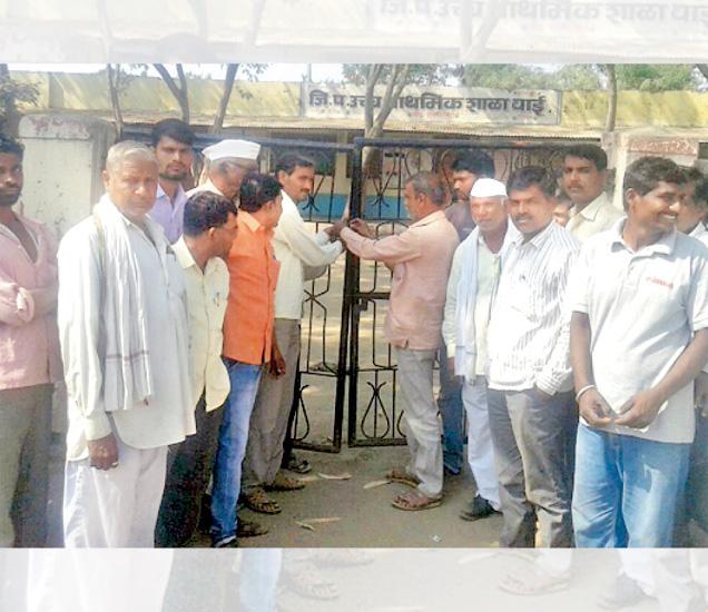राष्ट्रगीतानंतर शाळेच्या गेटला कुलूप ठोकताना वाईतील ग्रामस्थ. - Divya Marathi