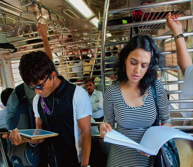 मुंबईतील लोकलमध्ये 'तनु वेड्स मनू' या सिनेमाची स्क्रिप्ट वाचताना स्वरा भास्कर. - Divya Marathi