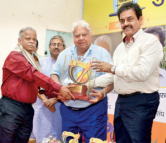 मान्यवरांच्या हस्ते क्रीडा पुरस्कार स्वीकारताना पत्रकार विनायक दळवी. - Divya Marathi
