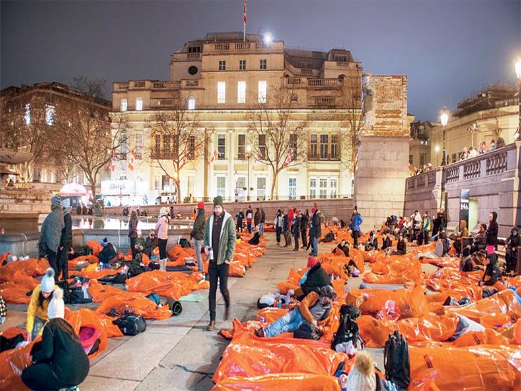 छायाचित्र लंडनच्या ट्राफल्गर स्क्वेअरचे आहे. येथे लोक वॉटरप्रूफ बेडिंग घेऊन पोहोचले होते. - Divya Marathi