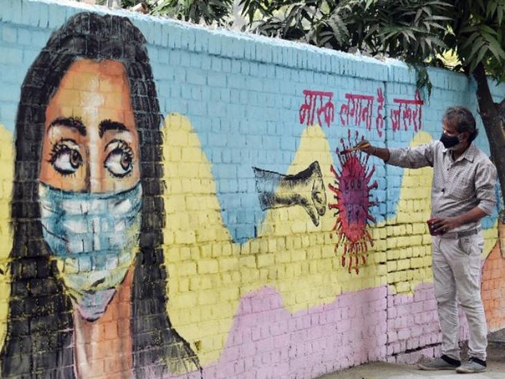 फोटो देशाची राजधानी दिल्लीचा आहे. कोरोनाची तिसरी लाट येथे सुरू झाली आहे. अशा परिस्थितीत एक कलाकार जागृकतेसाठी वॉल पेंटिंग करताना. - Divya Marathi