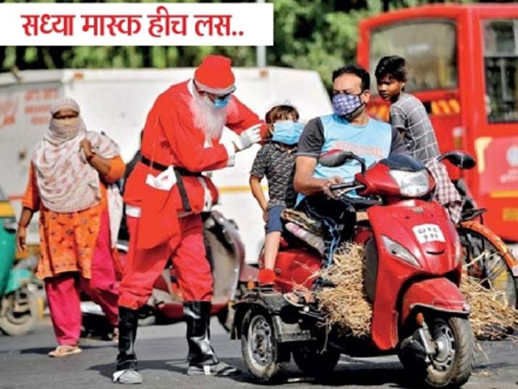 अहमदाबादेत विनामास्क जाणाऱ्या मुलास मास्क घालताना सांता. - Divya Marathi