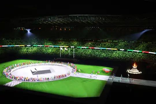 सर्व खेळाडू स्टेडियममध्ये एका वर्तुळात उभे आहेत. मधे म्युझिक बँड्स स्टेजवर परफॉर्म करत आहेत.