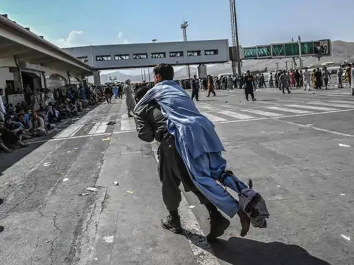 सोमवारी काबूल विमानतळावर गोळीबार झाला ज्यात 5 लोकांचा मृत्यू झाला. दरम्यान, बरेच जण जखमी झाले. दुसरी व्यक्ती जखमी व्यक्तीला सुरक्षित ठिकाणी घेऊन जात आहे