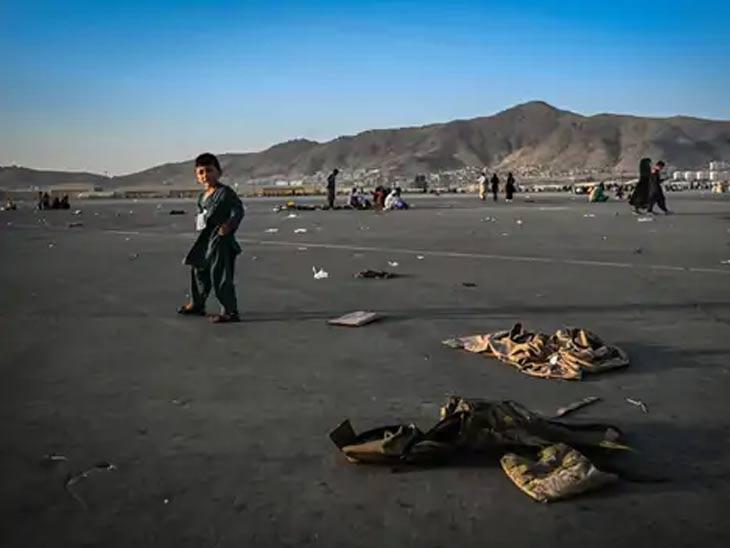काबूल विमानतळावर लष्कराच्या गणवेशाजवळून जाताना एक अफगाणी मुलगा...