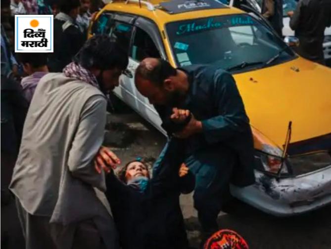 काबूल विमानतळाबाहेर तालिबानच्या हल्ल्यात जखमी झालेल्या एका महिलेला उचलताना दोन पुरुष. विमानतळावर प्रवेश करण्याचा प्रयत्न करणाऱ्या लोकांवर तालिबान्यांनी हल्ला केला.
