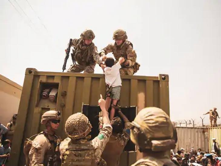 विमानतळाच्या आत मुलाला नेण्यास मदत करताना यूएस, यूके आणि तुर्कीचे सैनिक.