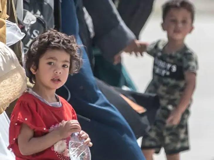 काबूल विमानतळावर आपल्या कुटुंबियांसह विमानात चढण्यासाठी वाट पाहताना अफगाणी मुले. विमानतळावरील प्रचंड गर्दीच्या गोंधळामुळे मुले कधीकधी भयंकर घाबरतात.