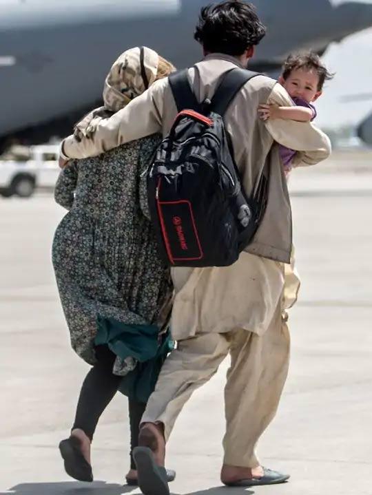 काबूल विमानतळावर अमेरिकन हवाई दल आपल्या नागरिकांसह अफगाण नागरिकांनाही बाहेर काढत आहे. एक अफगाणी नागरिक त्याची पत्नी आणि मुलासह विमानाच्या दिशेने कूच करताना...