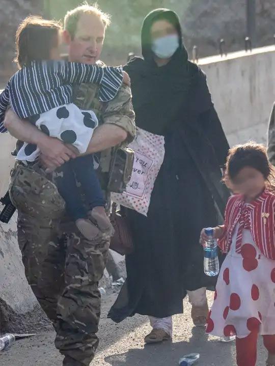 काबुल विमानतळावर एका अफगाण कुटुंबाला मदत करताना ब्रिटीश लष्कराचा एक सैनिक...
