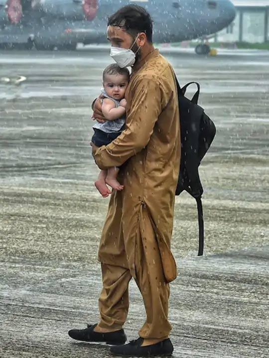 हिंडन एअरबेसवर पावसादरम्यान एक अफगाण शरणार्थी आपल्या मुलाला घेऊन जात आहे. यांच्याकडे भारतीय पासपोर्ट नसतानादेखील भारत सरकारने मानवता म्हणून त्याला भारतात येऊ दिले.