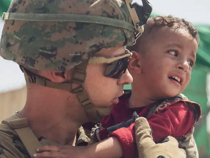 काबूलमधून लोकांना बाहेर काढताना एका रडत असलेल्या बाळाला सांभाळत असताना अमेरिकन सैनिक...