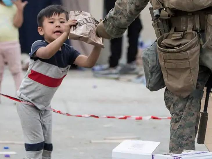 अमेरिकेसह इतर देशांचे सैनिकही मुलांच्या खाण्यापिण्याची विशेष काळजी घेत आहेत. काबुल विमानतळावर एका मुलाला अन्नाची पाकिटे देताना अमेरिकन सैनिक.