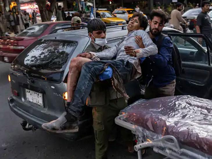 काबूलमधील रुग्णालयाबाहेर स्ट्रेचरवर जखमी व्यक्तीला घेऊन जात असलेले लोक.