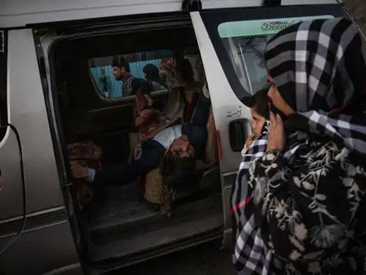 कारमध्ये पडलेल्या जखमी व्यक्तीकडे पाहणारी एक महिला आणि एक मूल. या हल्ल्यात अनेक लोक गंभीर जखमी झाले आहेत.