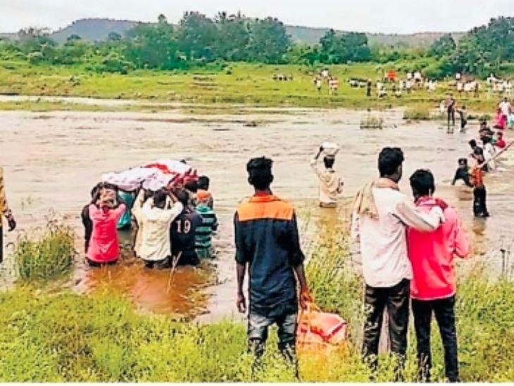 तरुणाच्या अंत्यविधीसाठी धनराट गावालगत पूर आलेल्या रंगावली नदीतून मार्ग काढताना ग्रामस्थ. - Divya Marathi