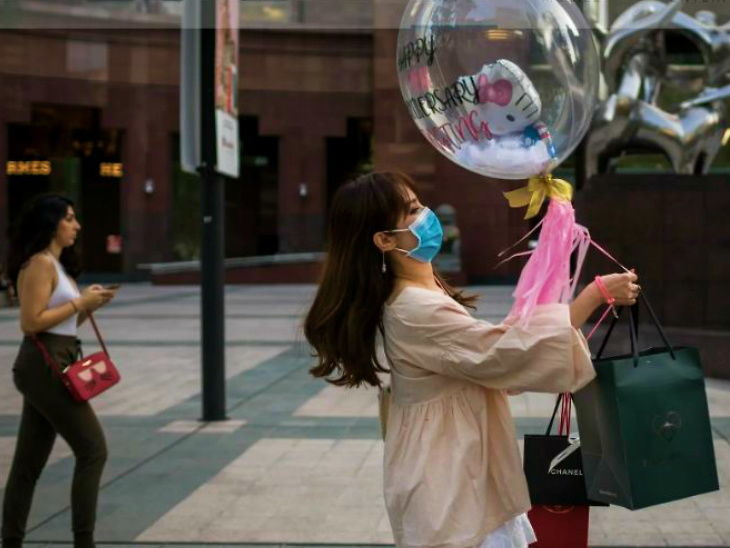 સિંગાપોરની એક બજારમાંથી પસાર થતી મહિલા. અહીં સંક્રમણ છૂપાવવા બદલ 6 મહિનાની સજાનો આદેશ અપાયો છે