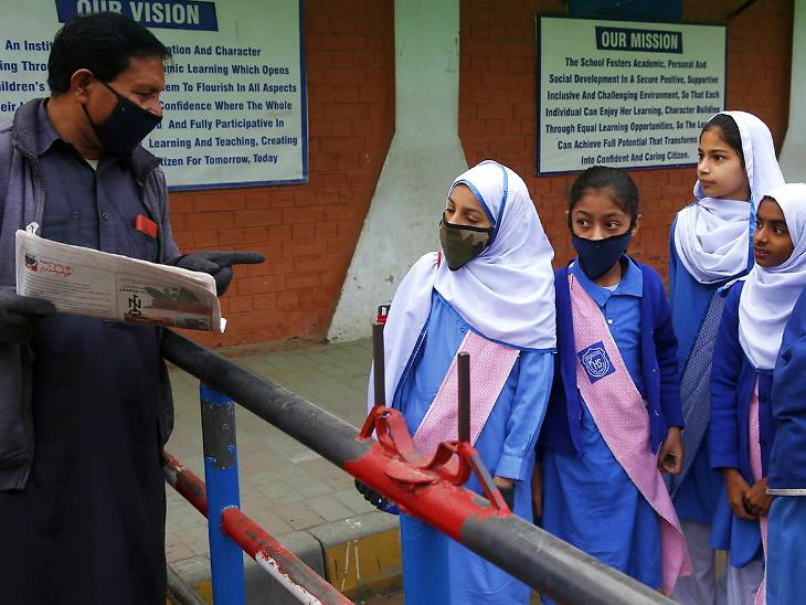 લાહોરની એક શાળા બહાર બાળકોને સંક્રમણથી બચવાના ઉપાય સૂચવતા કર્મચારી