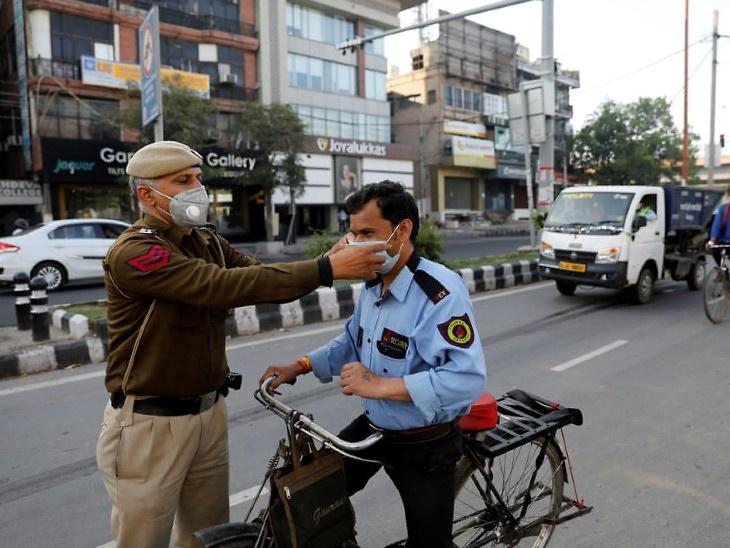 આ તસવીર દિલ્હીની છે. અહીં લોકડાઉન વચ્ચે ડ્યુટી પર જઈ રહેલા એક સિક્યોરિટી ગાર્ડને પોલીસકર્મી માસ્ક પહેરાવી રહ્યા છે - Divya Bhaskar
