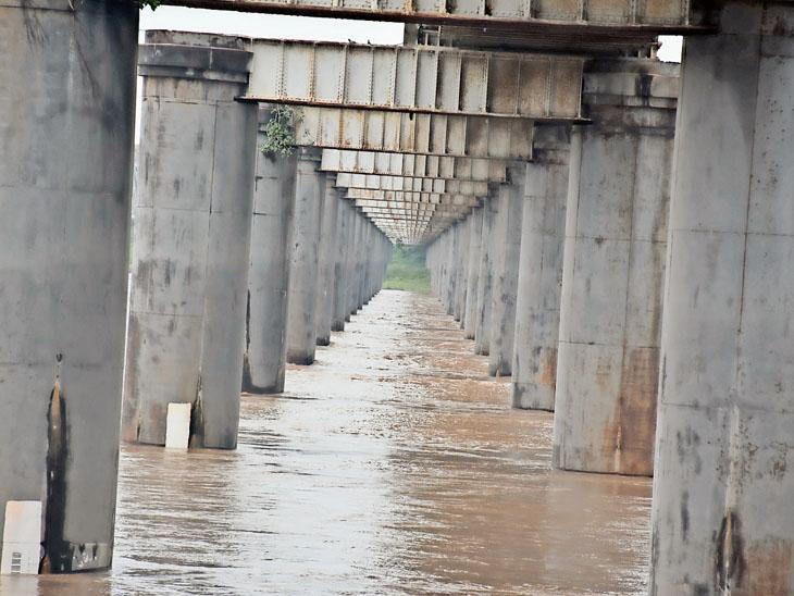 ગોલ્ડન બ્રિજની સાઇડના બે પીલર વચ્ચેથી નર્મદા નદીના પાણીના ધસમસતા વહેણની તસવીર. - Divya Bhaskar