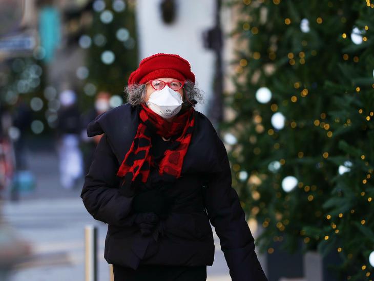 ગુરુવારે પેરિસમાં એક ક્રિસમસ ટ્રીની નજીકથી પસાર થતી મહિલા.