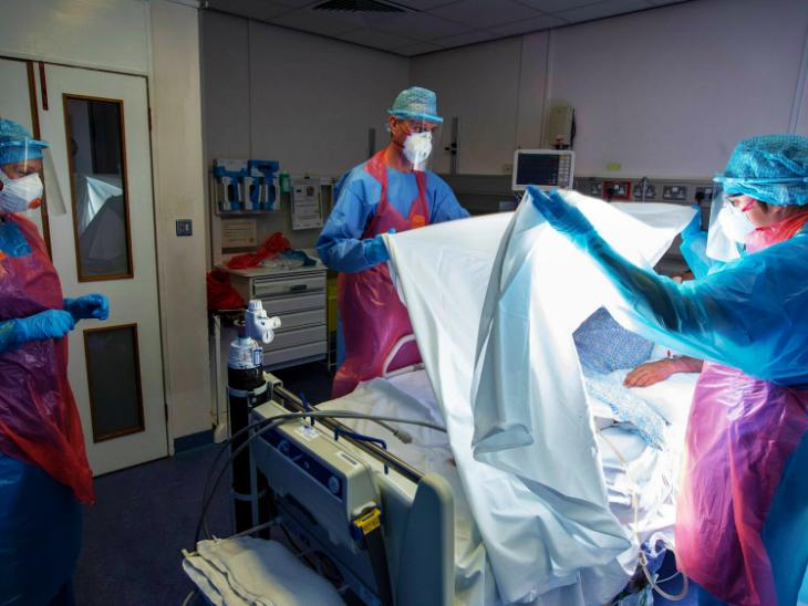 શુક્રવારે લંડનની એક હોસ્પિટલમાં દર્દીને વેન્ટિલેટર પર શિફ્ટ કરતાં આરોગ્યકર્મચારી.