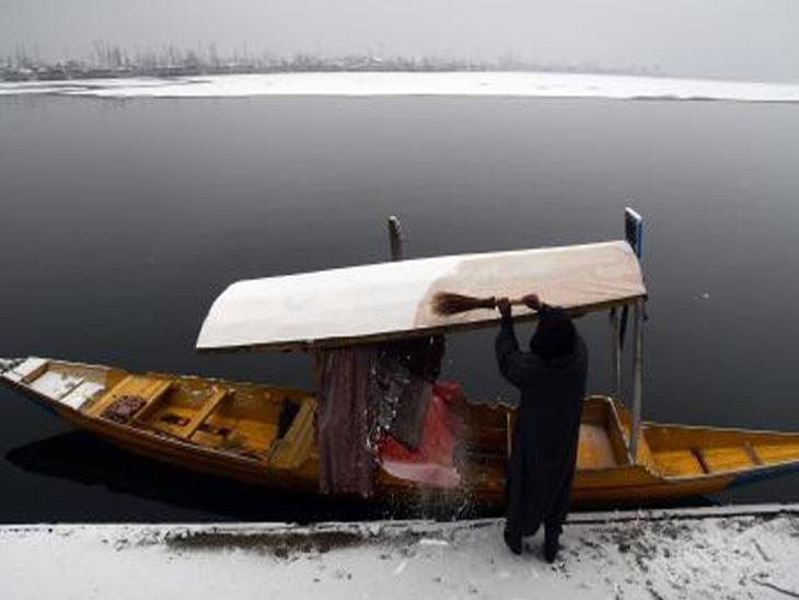 કાશ્મીરના પ્રખ્યાત દાલ લેકના કિનારે શિકારા પરથી બરફ સાફ કરી રહેલો વ્યક્તિ. હાડ થિજાવતી ઠંડી પછી અહીં દાલ લેક થીજી ગયું છે.