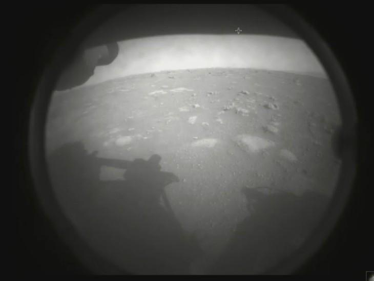 રોવરે આ પહેલો ફોટો નાસાને મોકલ્યો હતો. તેમાં મંગળની સપાટી અને રોવર બંને દેખાઇ રહ્યા છે.